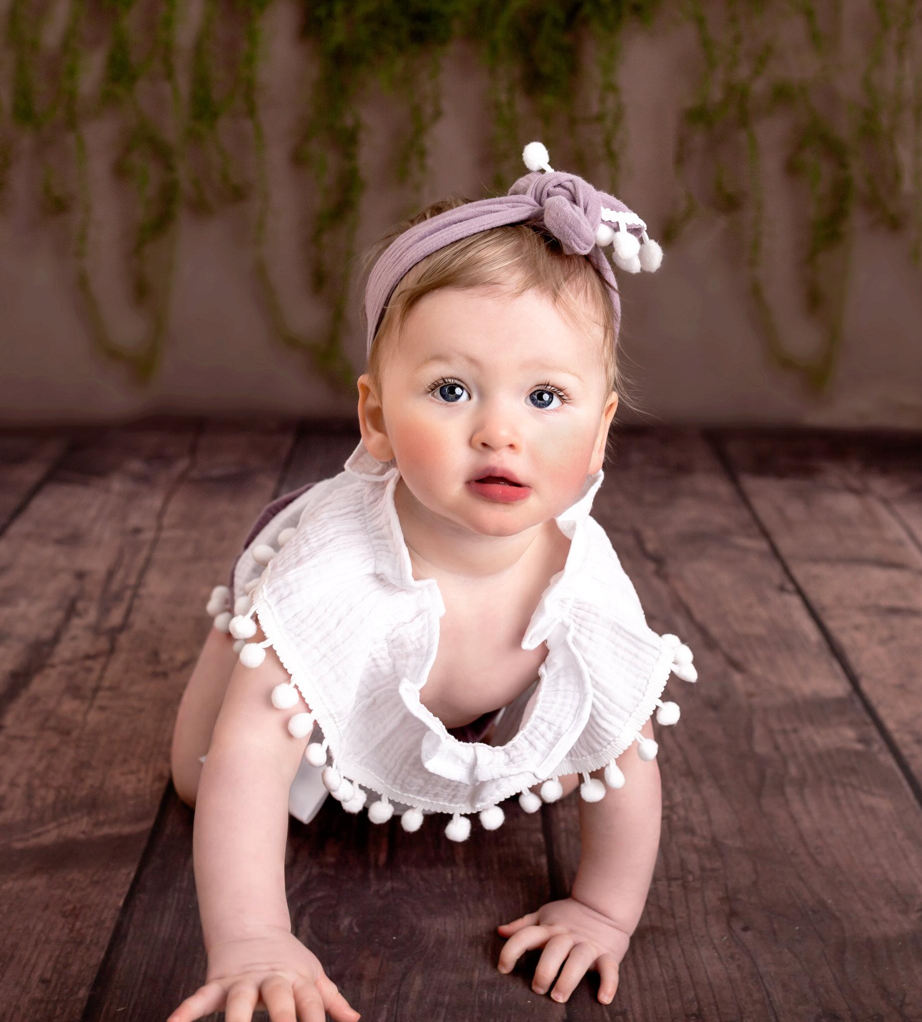 Baby girl crawls on the floor of Sevenoaks baby photography studio