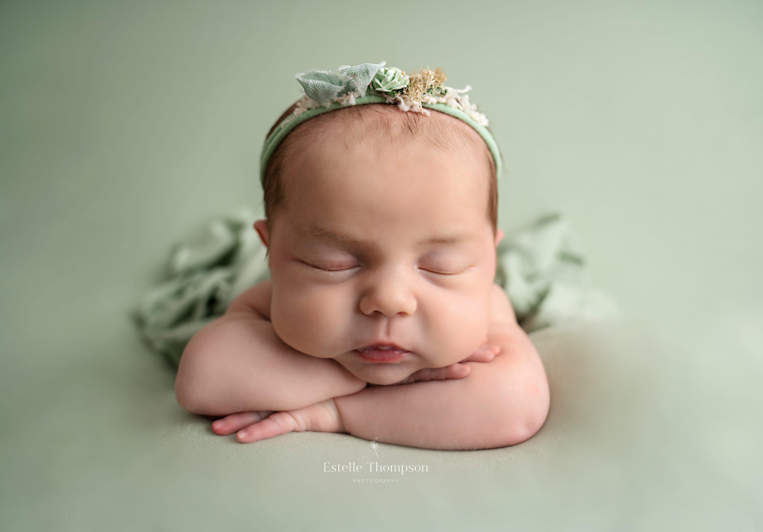 A newborn baby girl sleeps with her arms folded on a mint green blanket by Longfield Newborn Photography