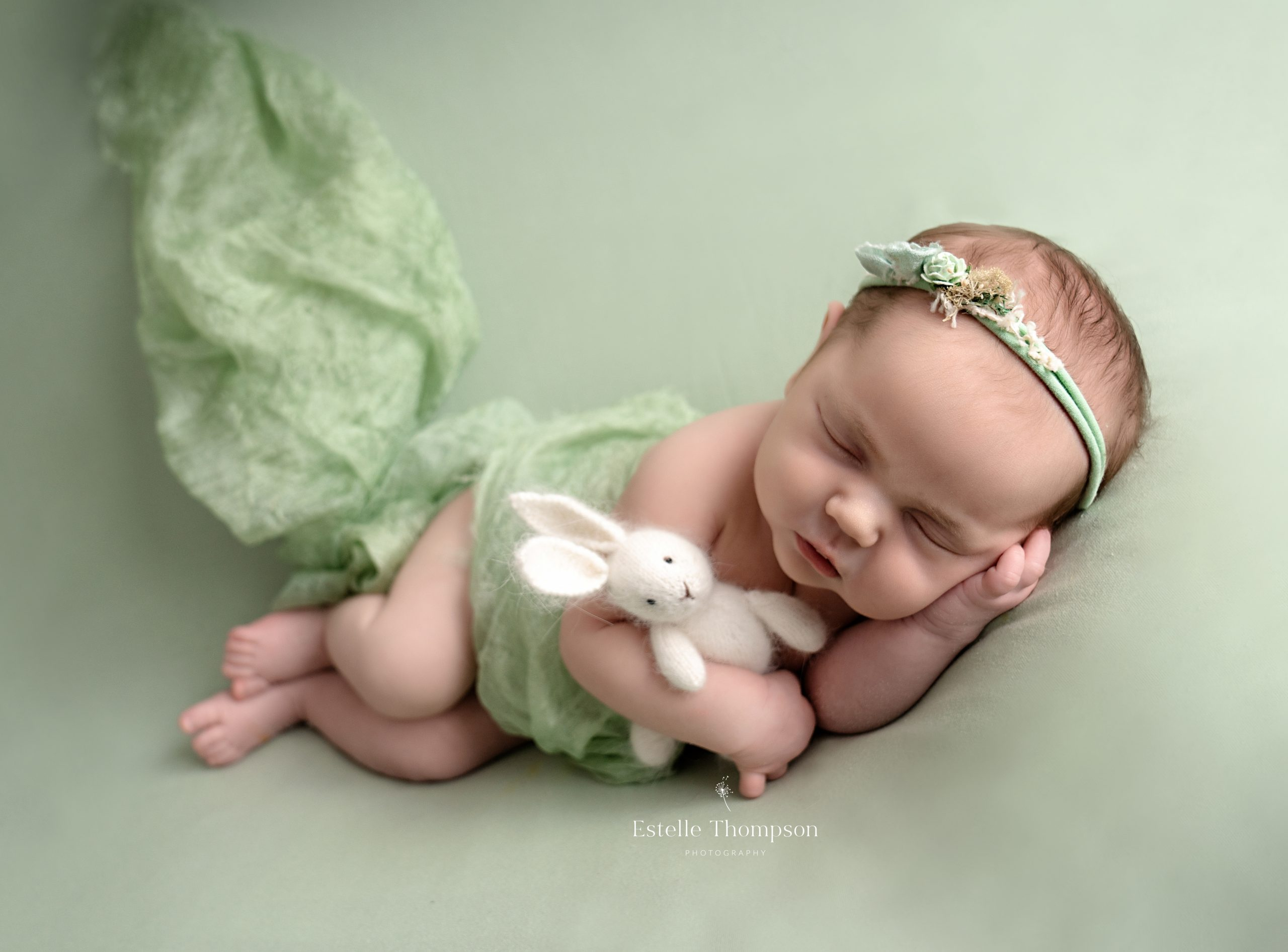 A newborn baby girl lays sleeping on a green blanket holding a white bunny by Sevenoaks newborn photographer
