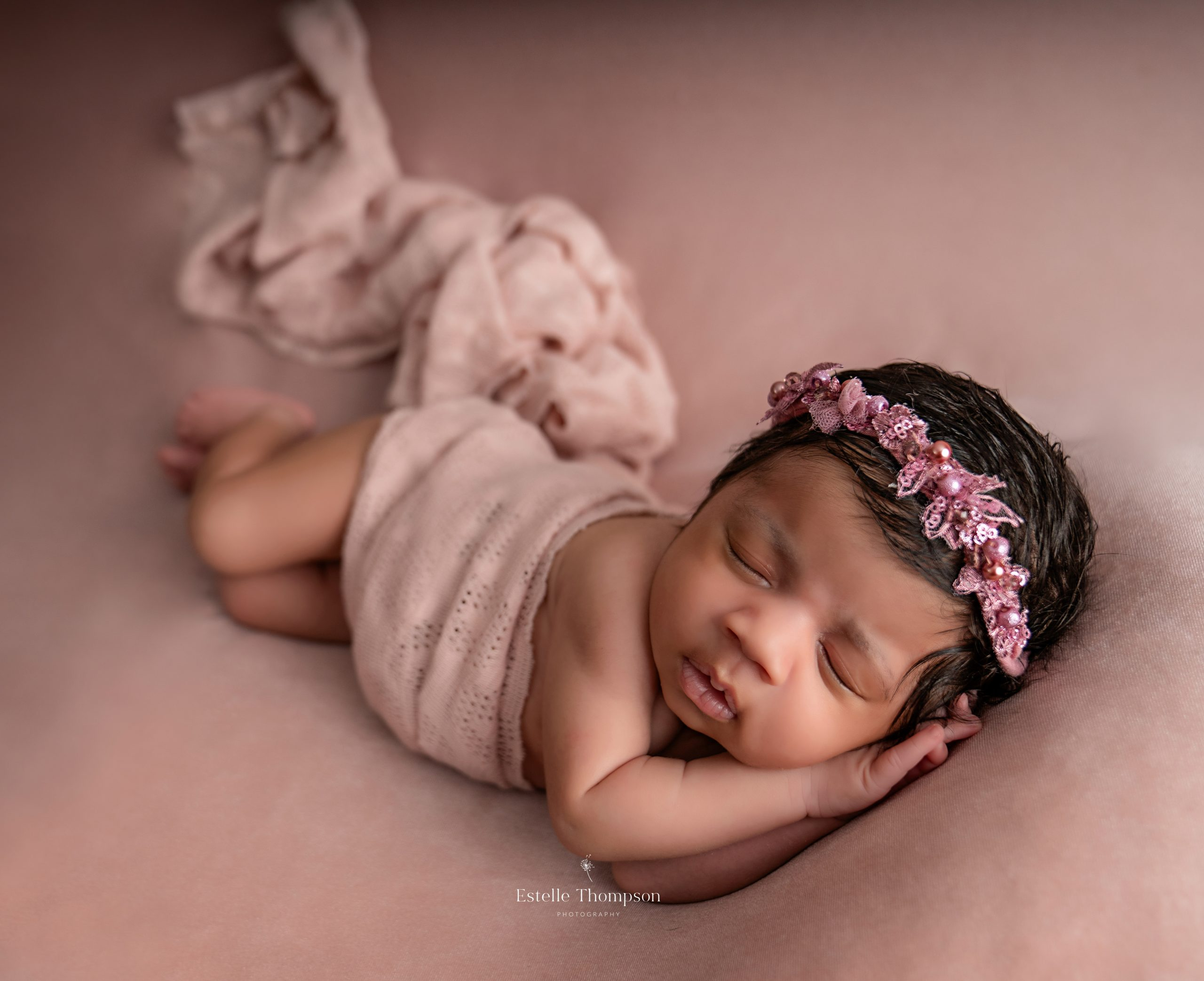 A newborn baby girl lays on a pink blanket sleeping by Kent Newborn photographer