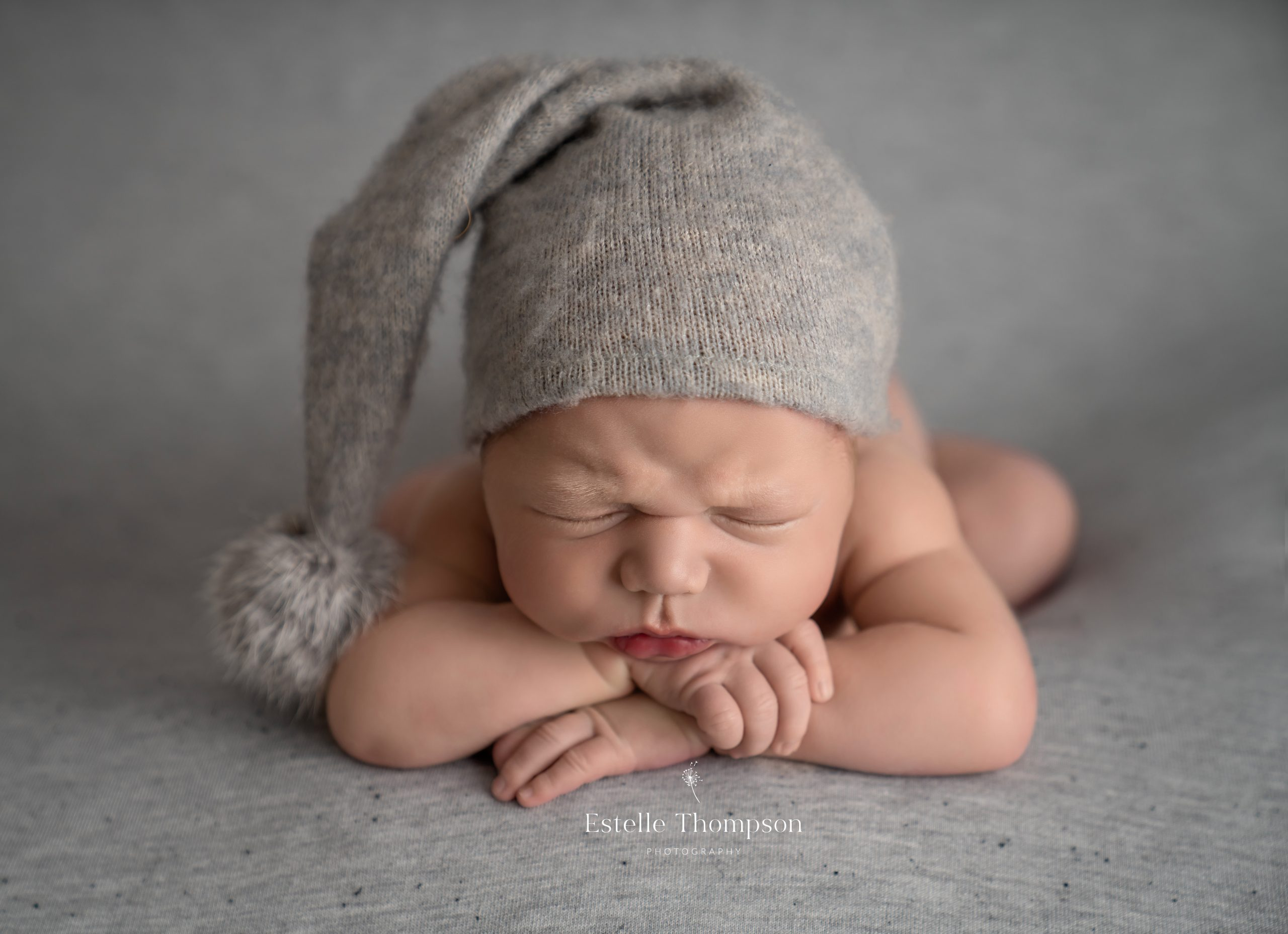 A baby boy sleeps frowing on a grey blanket taken by Sevenaoks newborn photographer