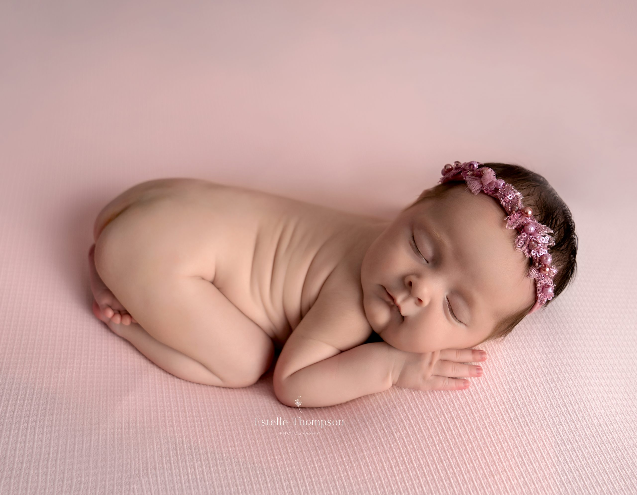 A newborn baby girl sleeps on a pink blanket by Sevenoaks newborn photographer