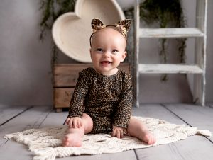 Baby girl wearing a leopard print romper sits on the floor laughing by Sevenoaks baby photographer