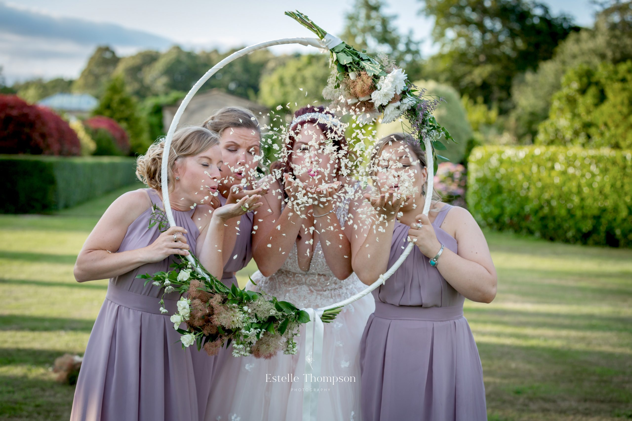 Bride and bridesmaids blow confetti through a floral hoop by wedding photographer kent