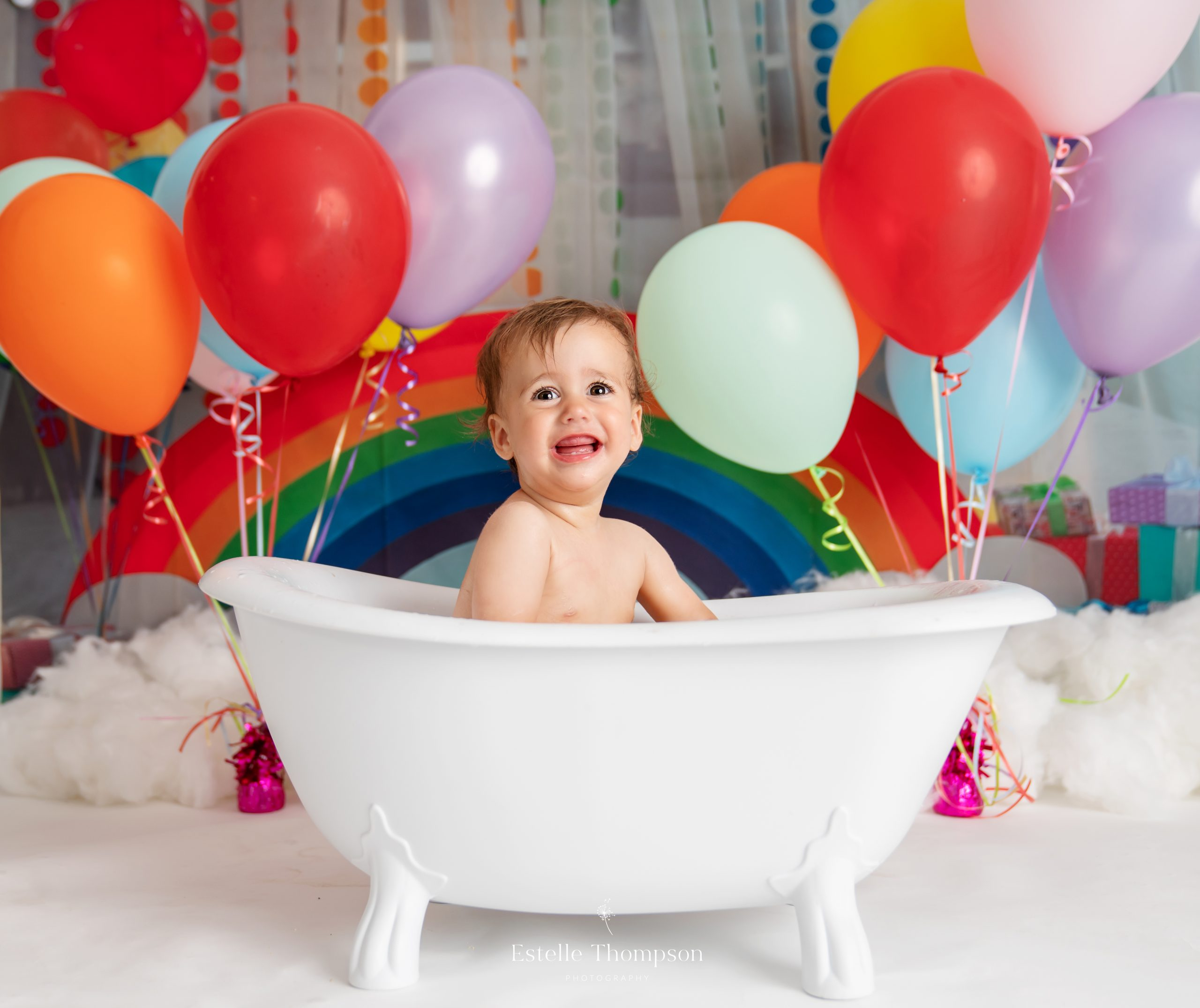 Asmiling baby sits in the roll top bath after her Dartford Cake Smash photoshoot