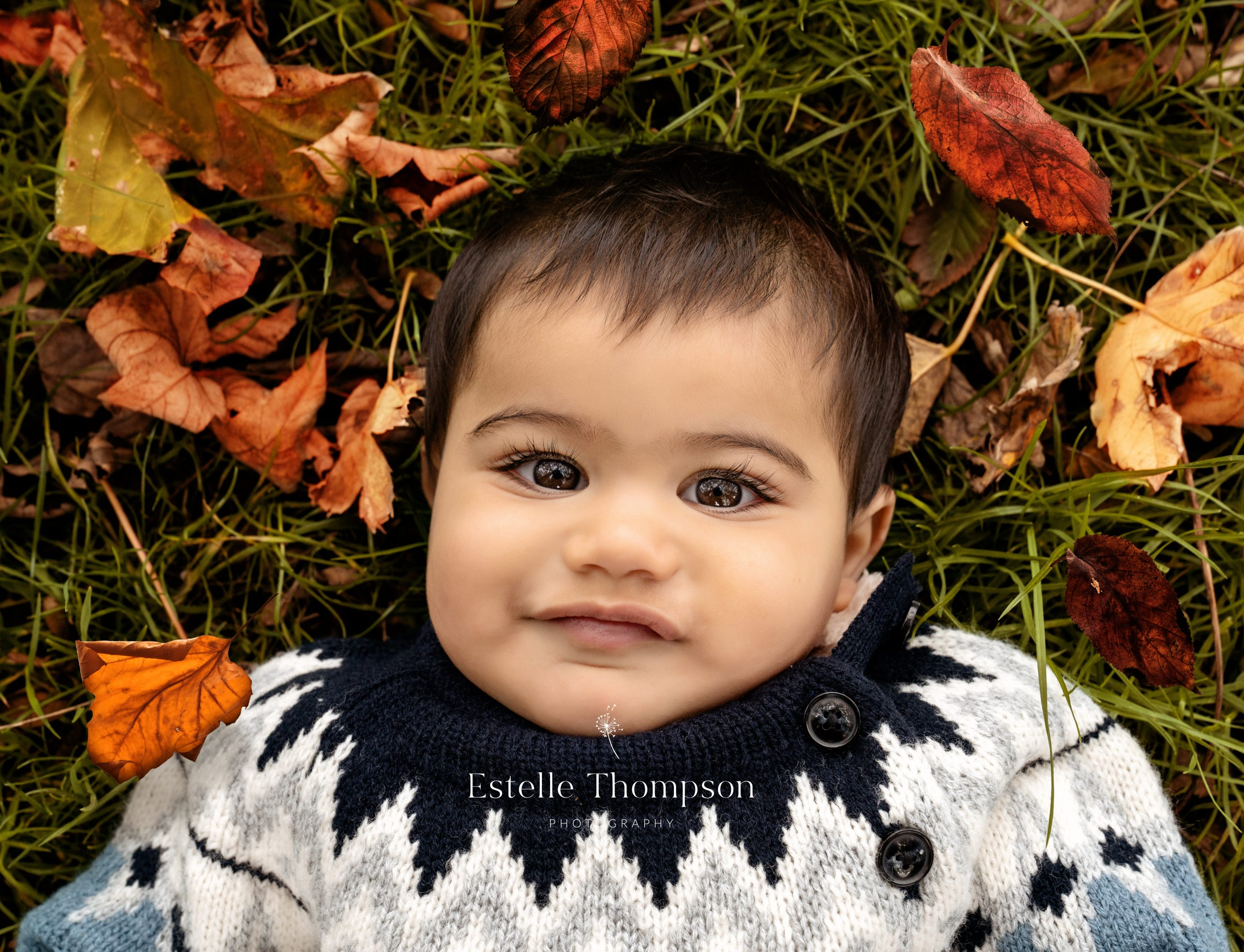 A baby boy lays on the floor in the autumn leaves on a Longfield family photographer shoot