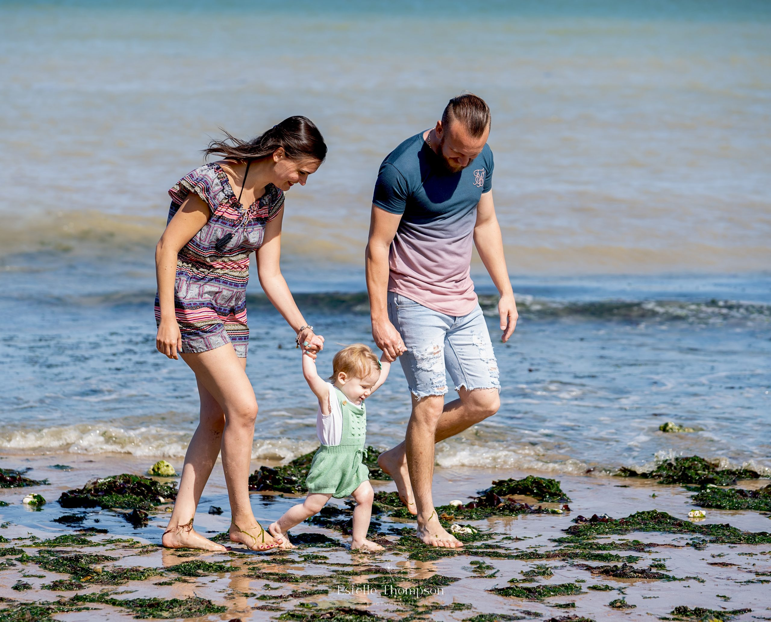 A Mum and Dad walk along the beach holding the hand of their baby daughter for a Kent family photographer