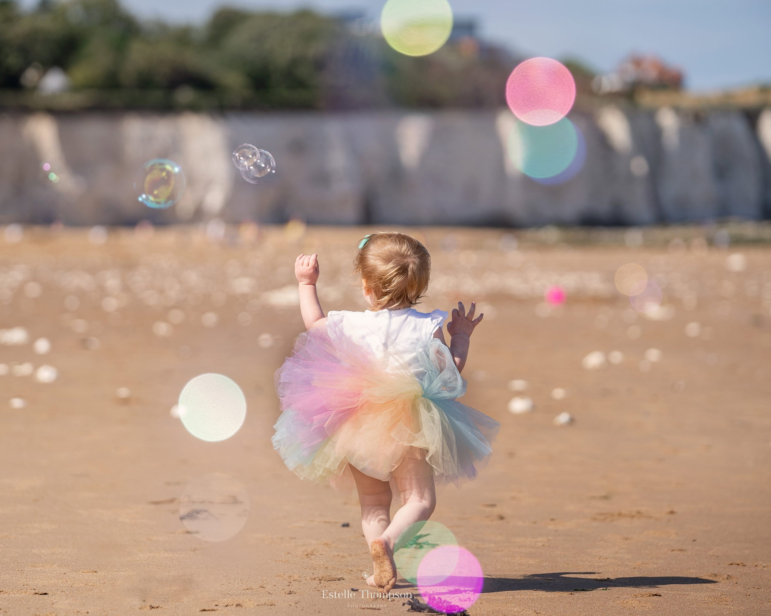 A baby wearing a rainbow tutu is dancing on the beach for a Kent family photoshoot