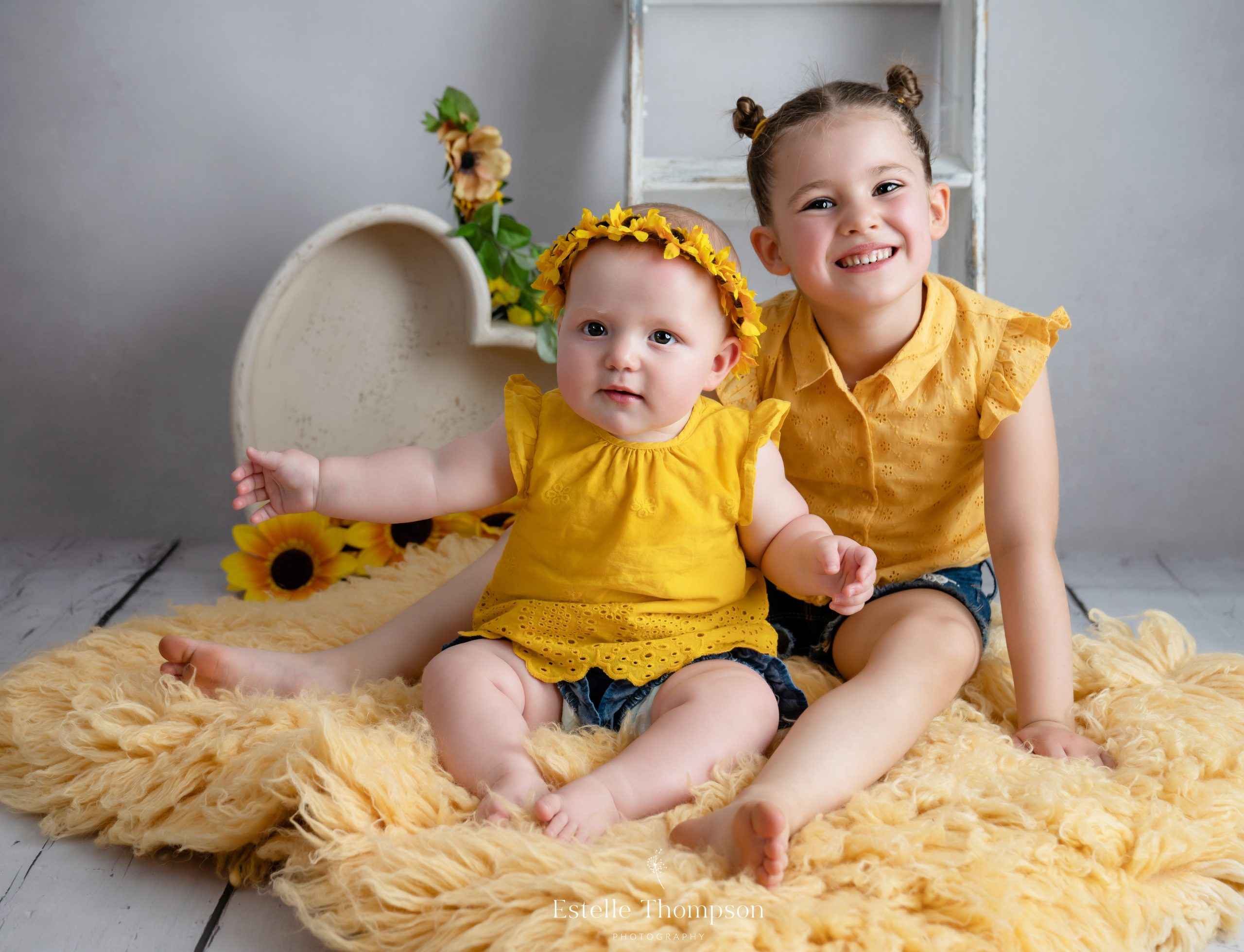 Two sisters dressed in yellow sit to have their photograph taken at a sevenoaks baby photography studio