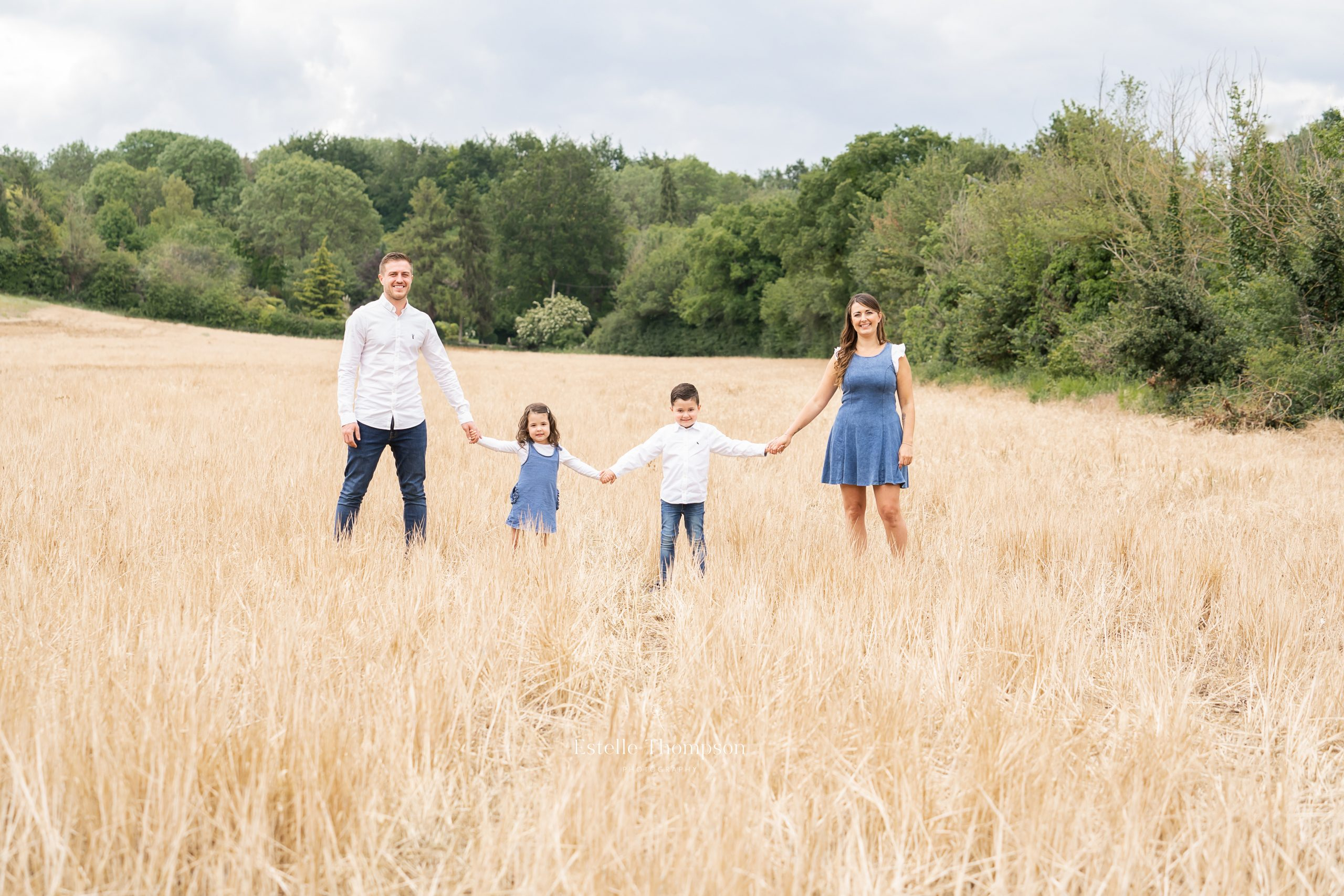 A family of mum dad daughter and son stand in front of a gate in the countryside for a Kent family photoshoot