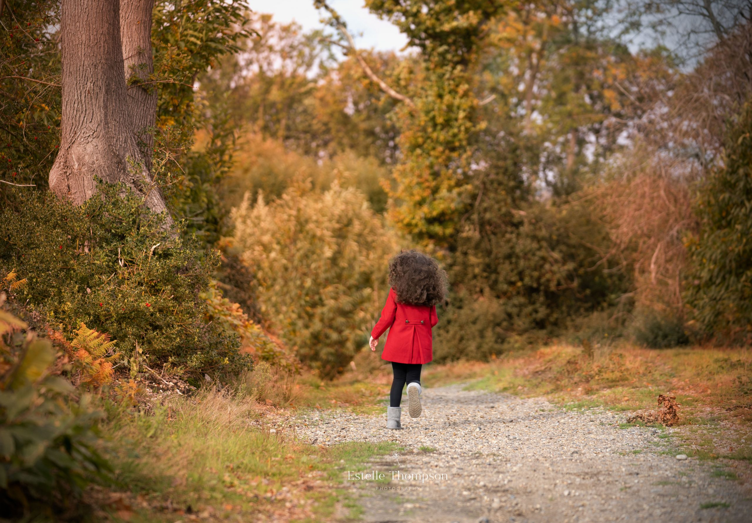A girl runs through the woods wearing a red coat with a Sevenoaks family photographer in Kent