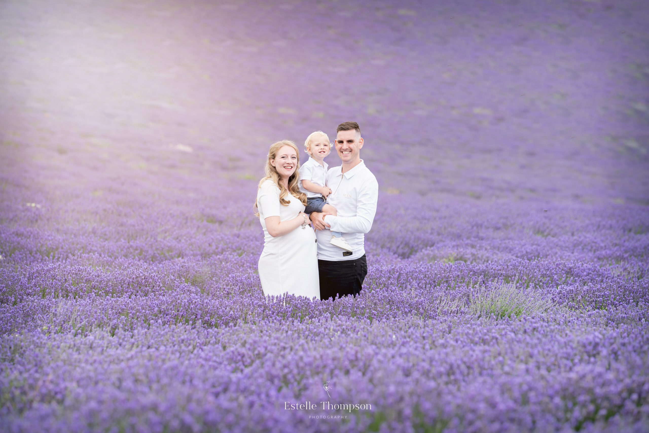A pregnant mum and her husband holding their son son stand in a lavender field in Sevenoaks Kent for a family photo