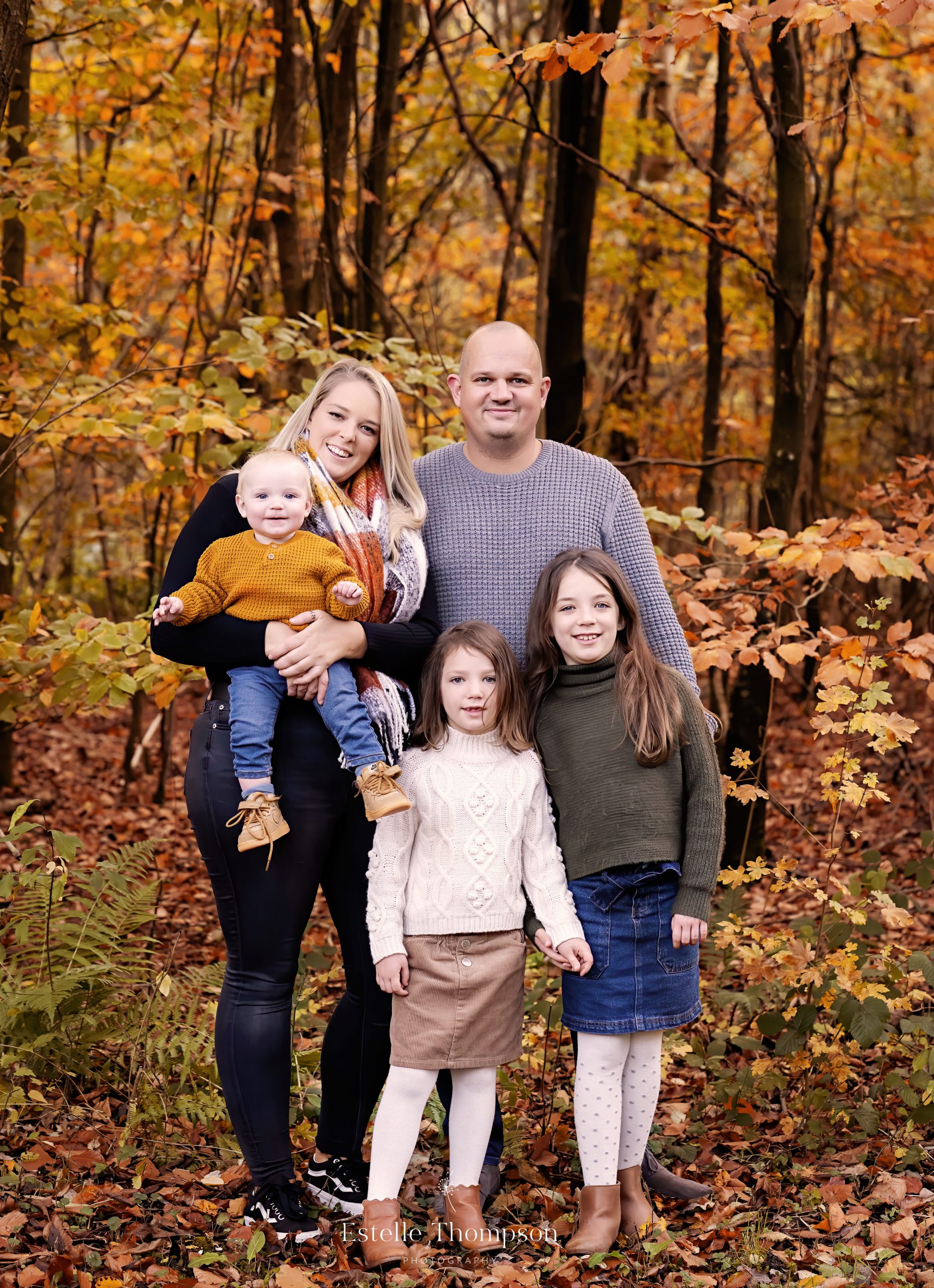 A family stand in the woods in Autumn for a Sevenoaks family photoshoot
