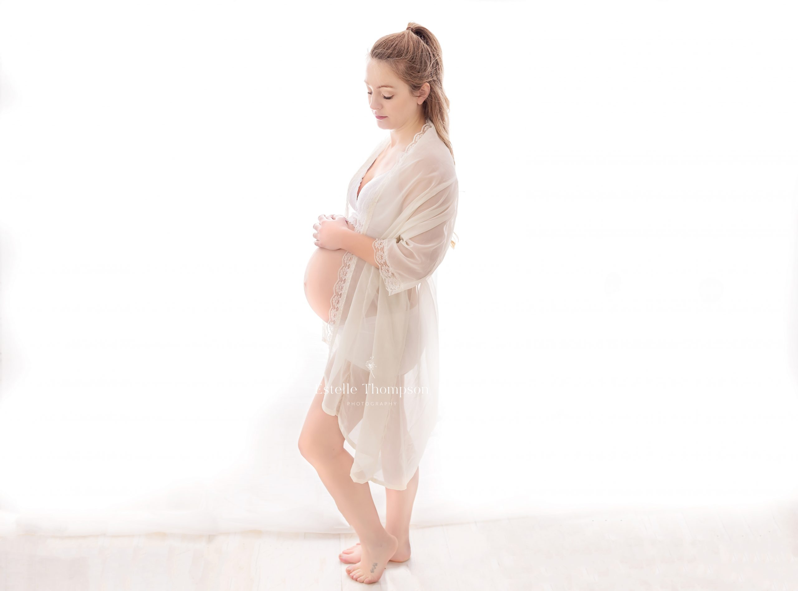 Pregnant lady stands in front of a white curtain in kent maternity photography studio