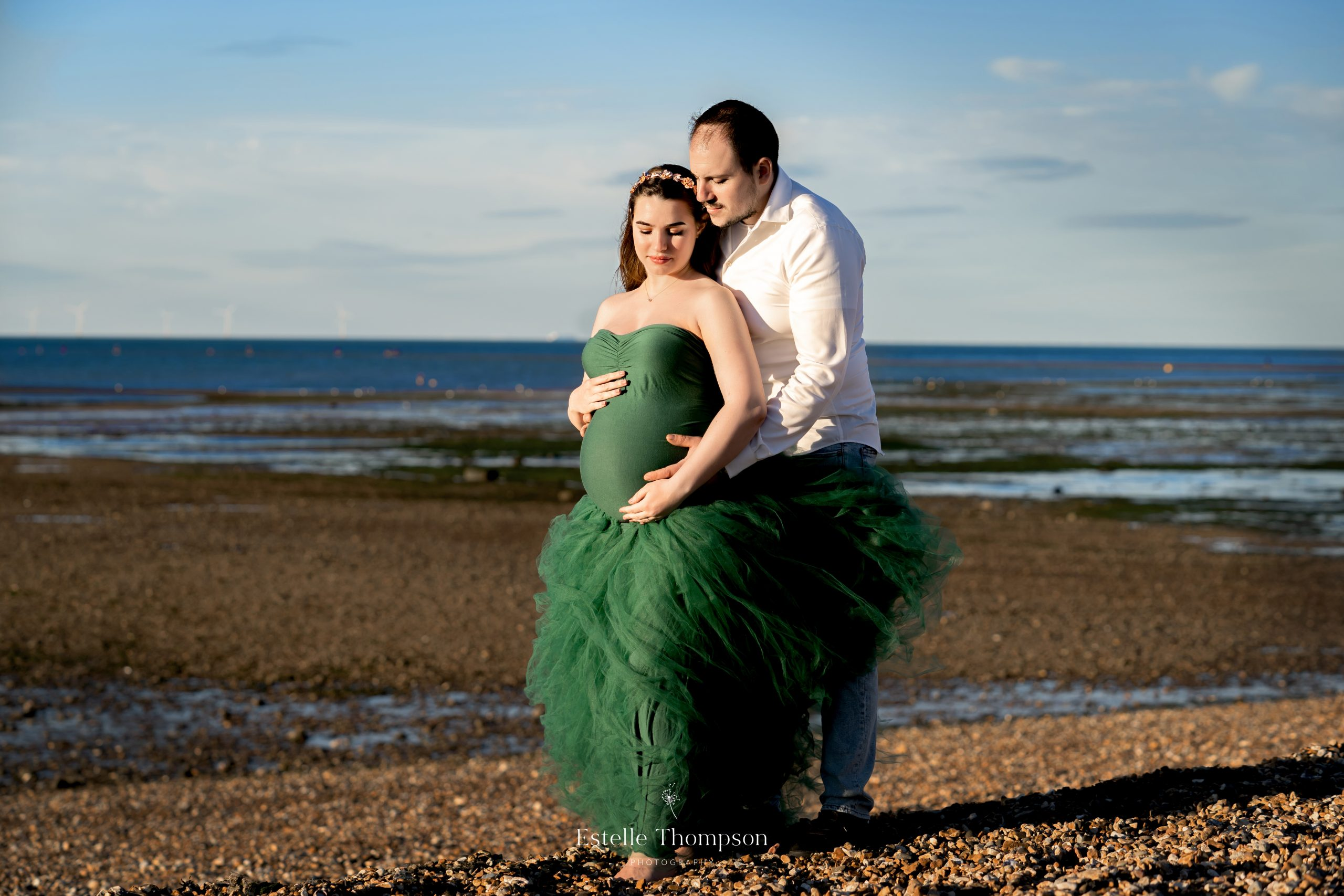 Pregnant lady stands on a beach with her husband gazing at her bump being photographed by kent maternity photographerp