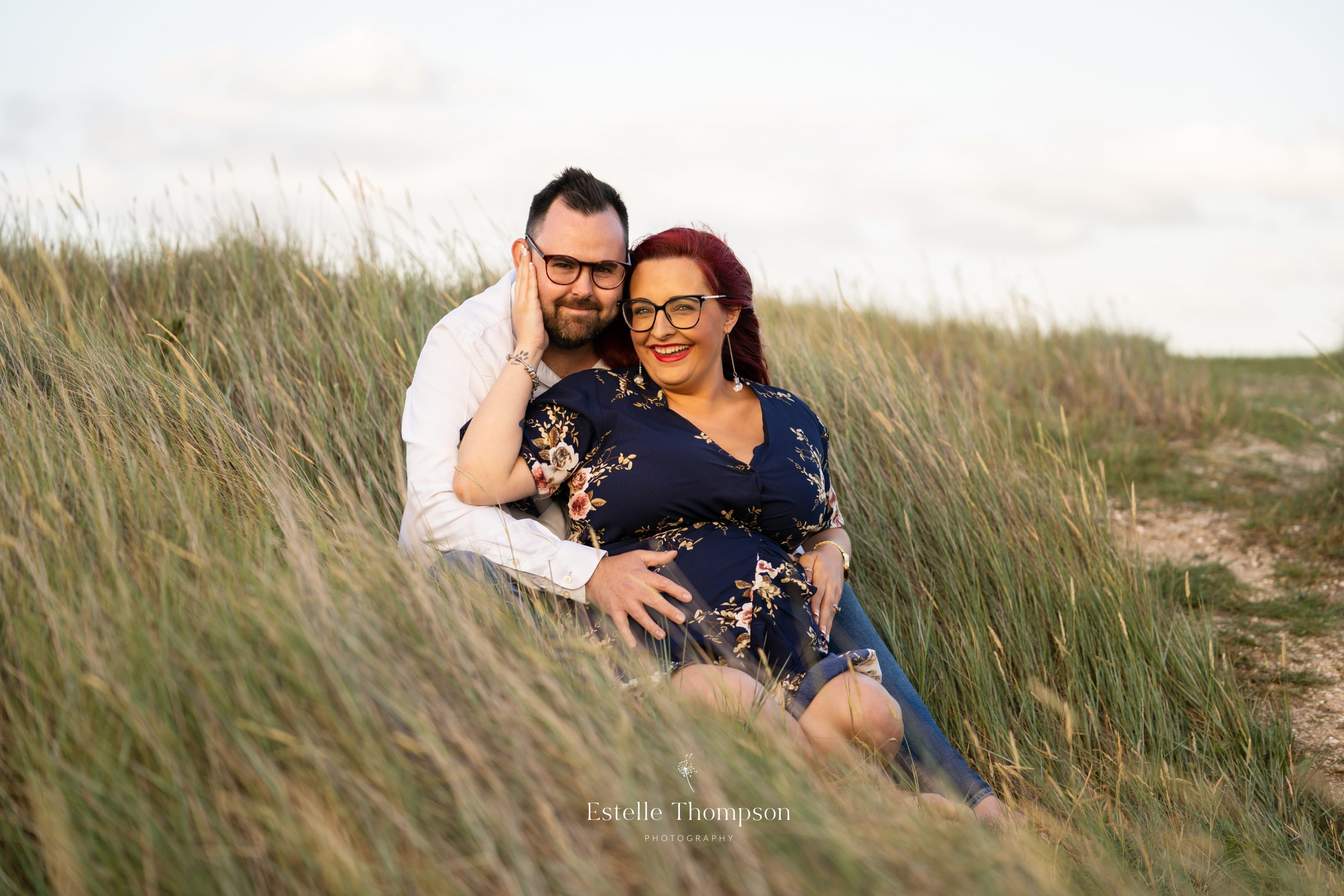 A pregnant lady sits on a sand due with her husband by her kent maternity photographer