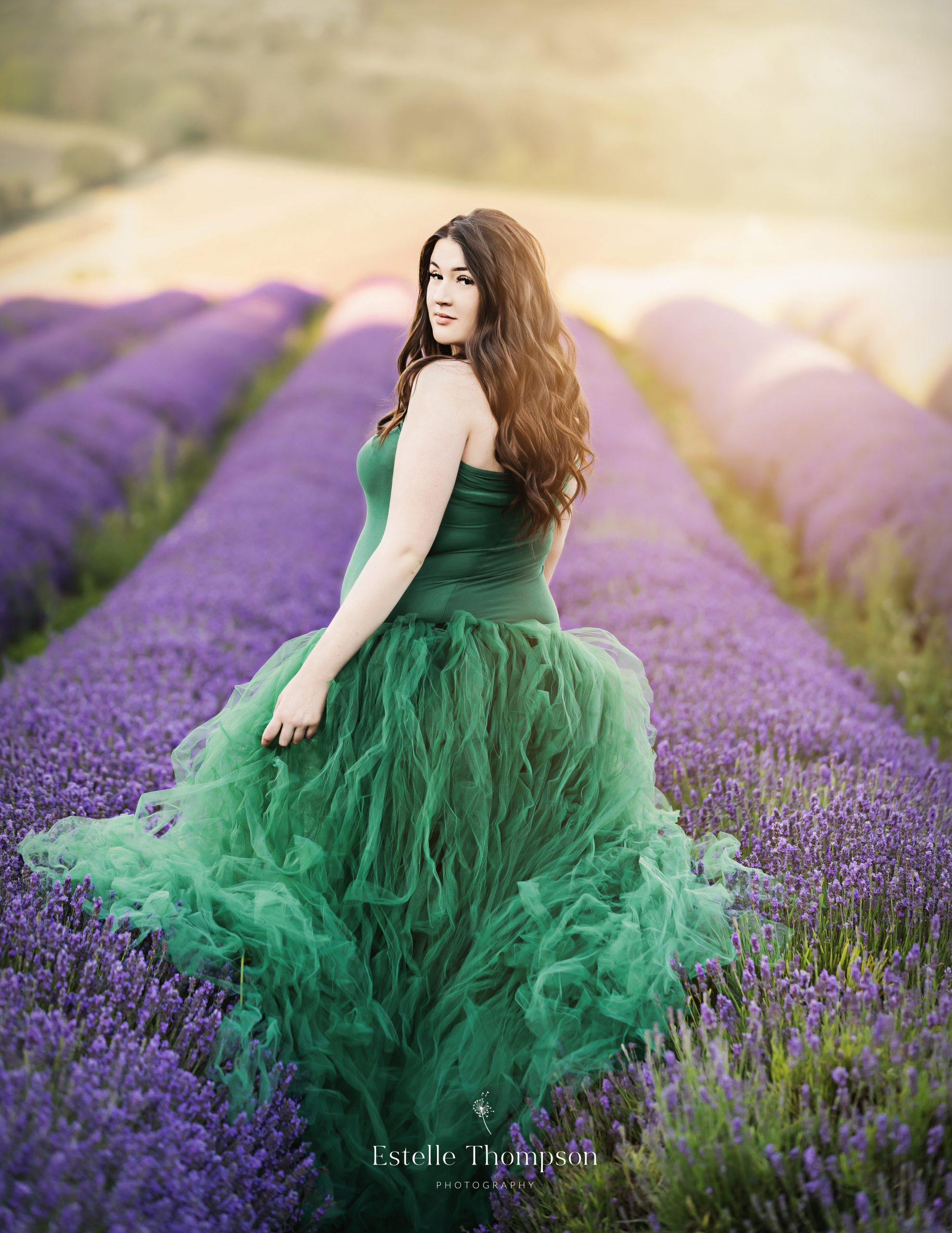 Aa pregnant lady walks through a lavender field on maternity photoshoot in kent