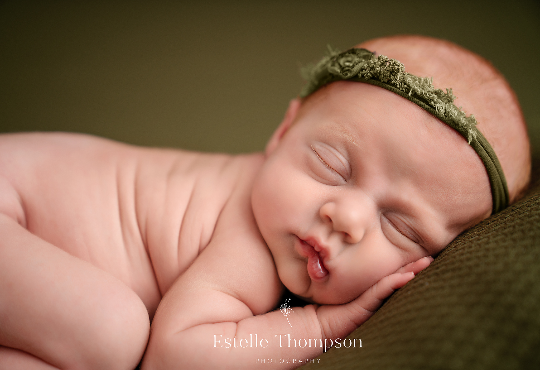 a newborn baby girl lays on a green blanket in a sevenoaks newborn photographers studio