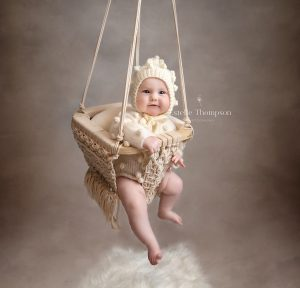 baby sitting in a macrame swing being photographed by a sevenoaks baby photographer