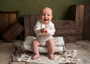 baby boy sitting on a bed at a baby photoshoot in sevenoaks
