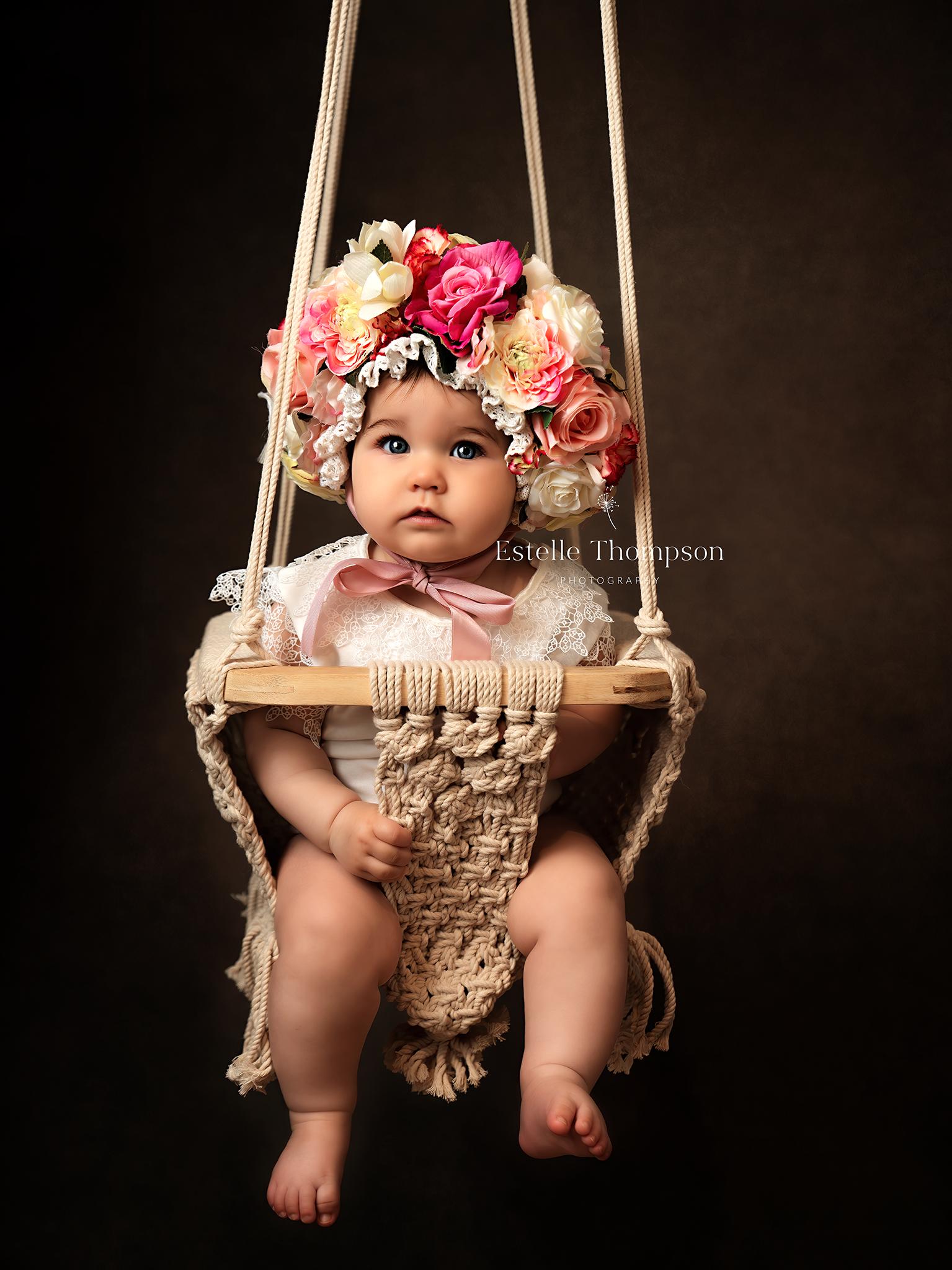 Baby in a swing in Sevenokas baby photographer studio